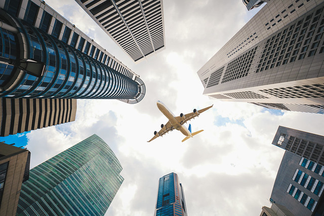 Tall city buildings and a plane flying overhead