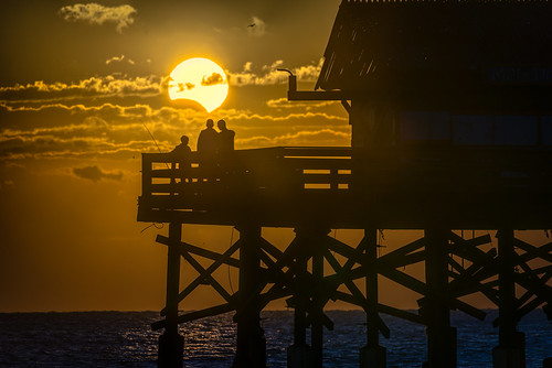astronomy candid centralflorida cloud cocoa dawn eclipse existinglight florida landscape moon ocean orange people peoplephotography sky sunrise usa water weather dock fishing pier solareclipse partial edrosackcom