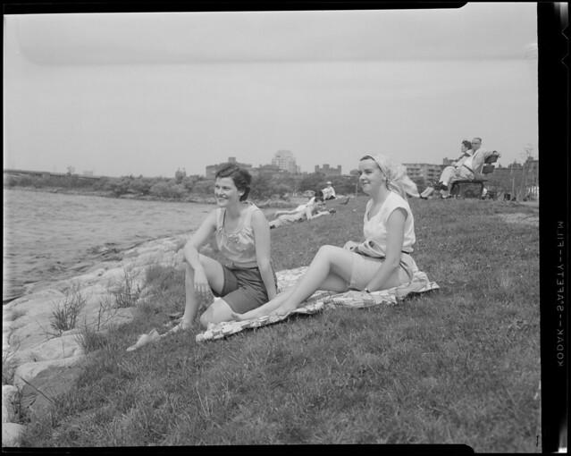 Women sit on grass next to water