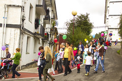 En la imagen se puede ver cómo padres, madres, niños y niñas bajan por el camino escolar