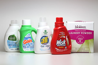 Five laundry detergents lined up on white table | by yourbestdigs