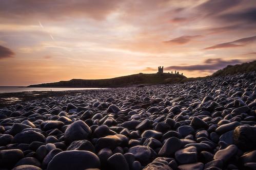 yellow sunriseatdunstanburghcastle northumberland england landscape seascape seacoast sea rocks sunrise beach castle gb uk