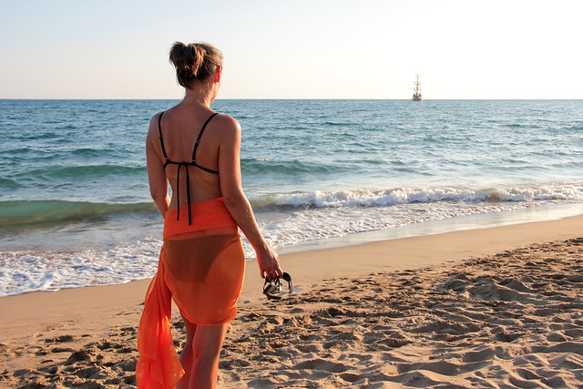 Woman in an orange scarf on the beach 9
