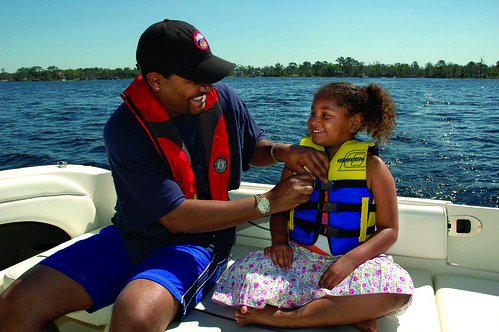 Photo of father helping young daughter put on a personal flotation device