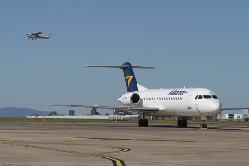 Light plane passes over parked Alliance Airlines Fokker F70 VH-QQR