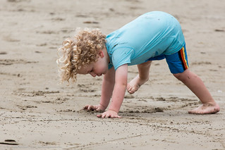 Cute very young little boy or maybe a girl with curly hair attempts a handstand in the sand on the beach.  People watching, on Morro Strand State Beach, | by mikebaird