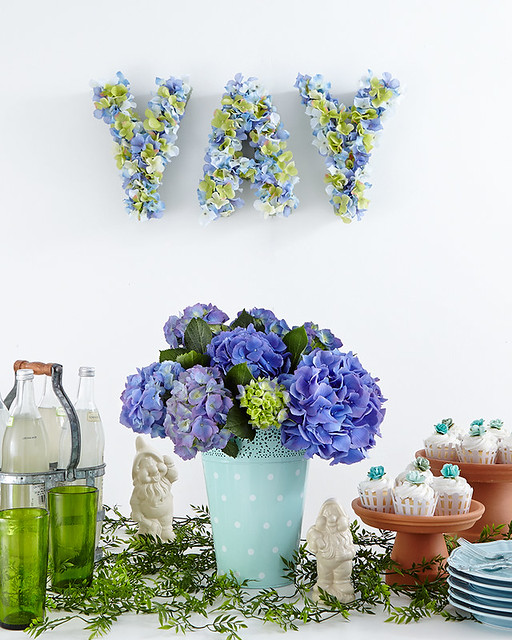 hydrangeas in a blue vase with cupcakes and Disney dwarves with flower sign on wall