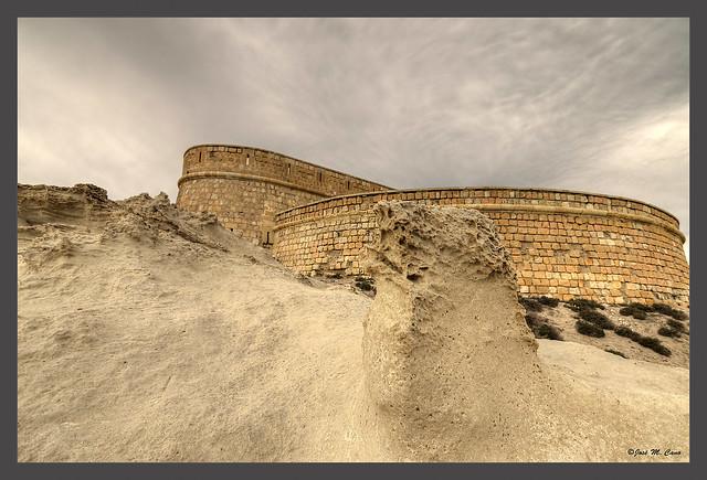 Tras las rocas, la muralla del castillo