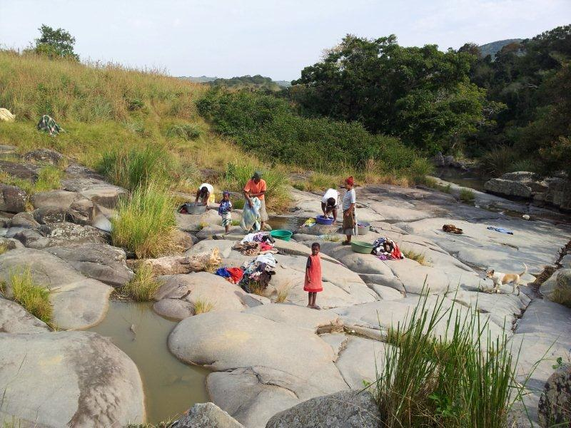 Community members washing clothes at a nearby river