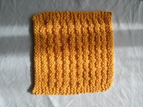 A yellow knitted dishcloth in a textured waffle pattern.