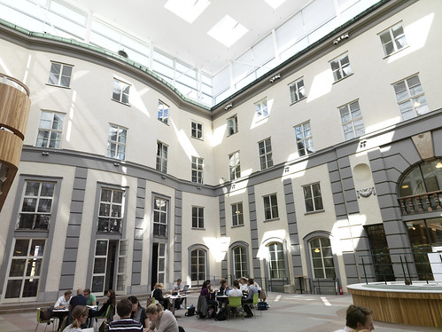 Atrium med elever som studerar vid fasad
