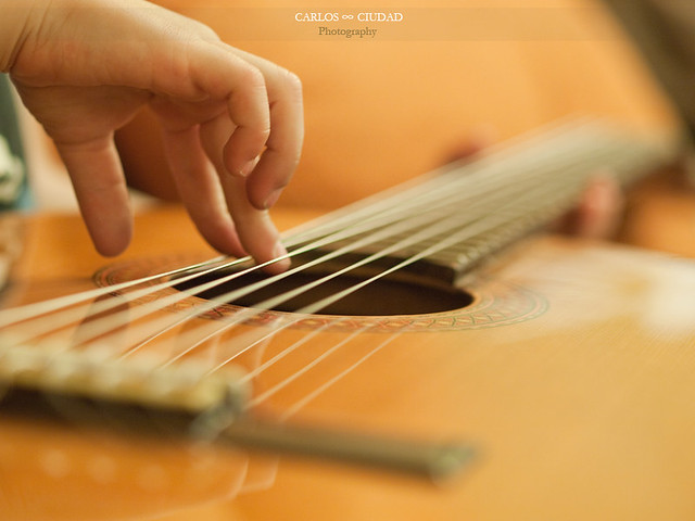 Detail of hands of a child learning to play the guitar
