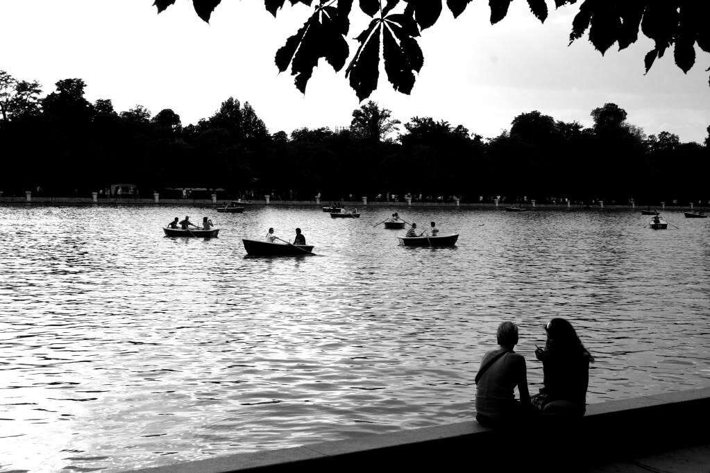 People relaxing on the lake in El Parque Retiro in Madrid, Spain.