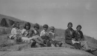 Group of children and two women sitting on a large rock, Fort Chipewyan, Alberta / Deux femmes et un groupe d'enfants assis sur un rocher, fort Chipewyan (Alberta)
