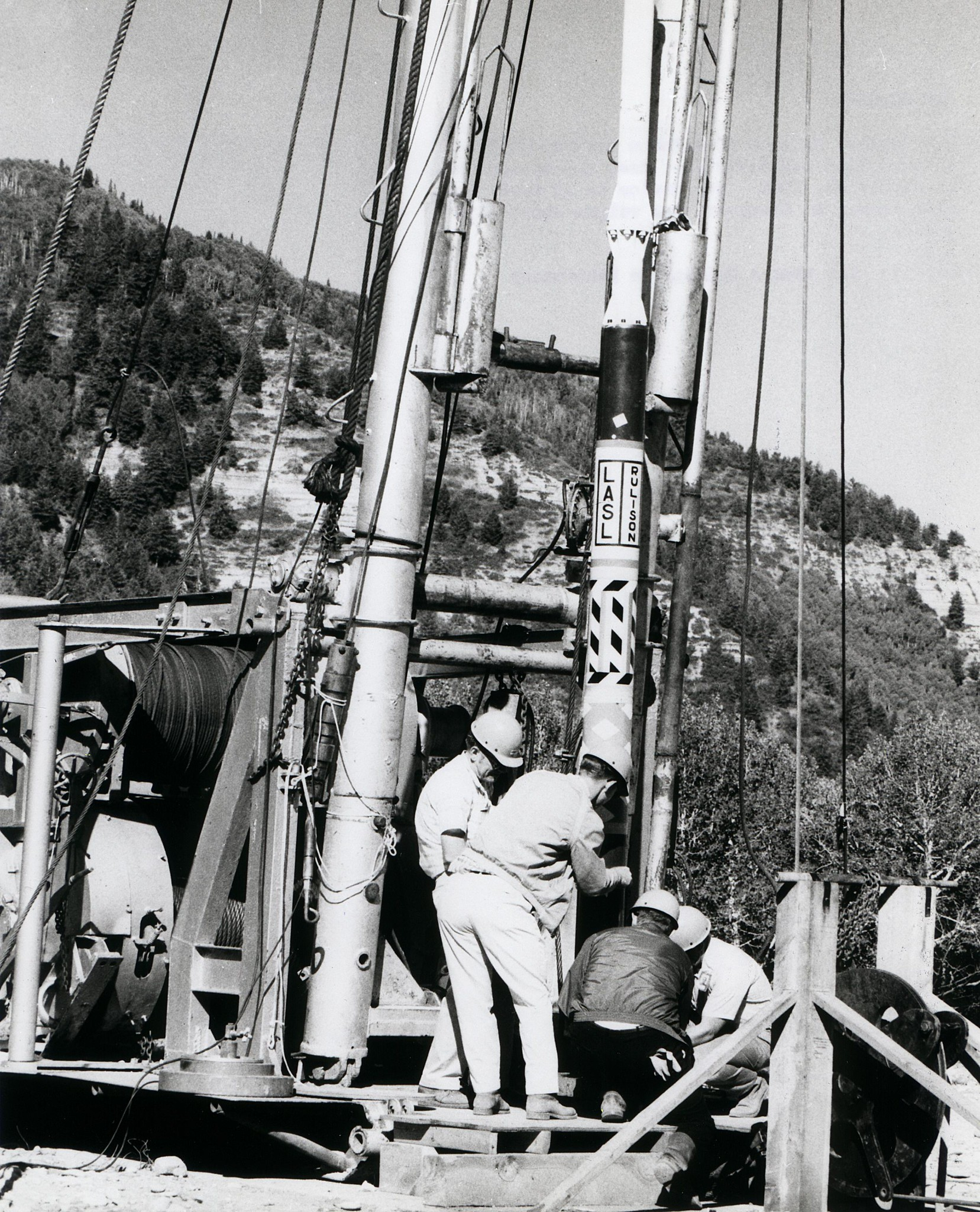 Black and white image of male-presenting workers in hardhats and coveralls working with a crane and many steel cables in a mountain landscape.