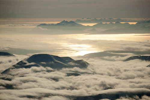 Svalbard mountain tops in the clouds seen from the sky   by Kitty Terwolbeck