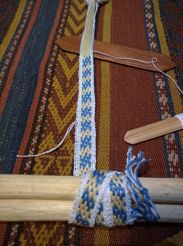 Irieknit backstrap weaving narrow tanka cho'ro double motif band with blue Andean crosses and yellow shells white border.  A mahogany sword rests in the shed and a narrow shuttle with white weft is to the right.  The cloth sticks are resting on a handwoven patterned cloth with handdyed yarn.