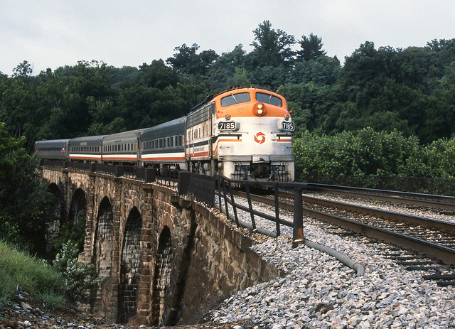 Maryland Area Rail Commuter (MARC) push-pull commuter train led by an old EMD F7A # 7185, is seen crossing the Thomas Viaduct on it's trip to Baltimore, Maryland, August 1988