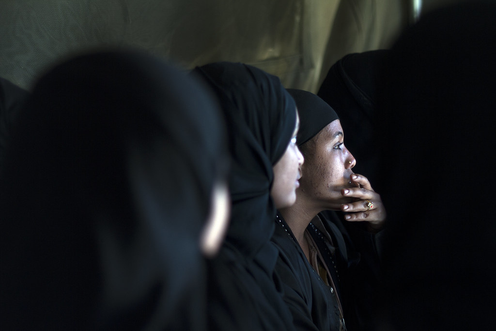 A group of women Saudi returnees wait for their turn to disembark for their respective home areas after receiving orientation by by UNICEF staff.