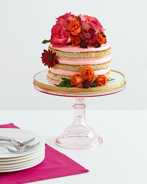 pink and orange roses and daisies on a frosted cake