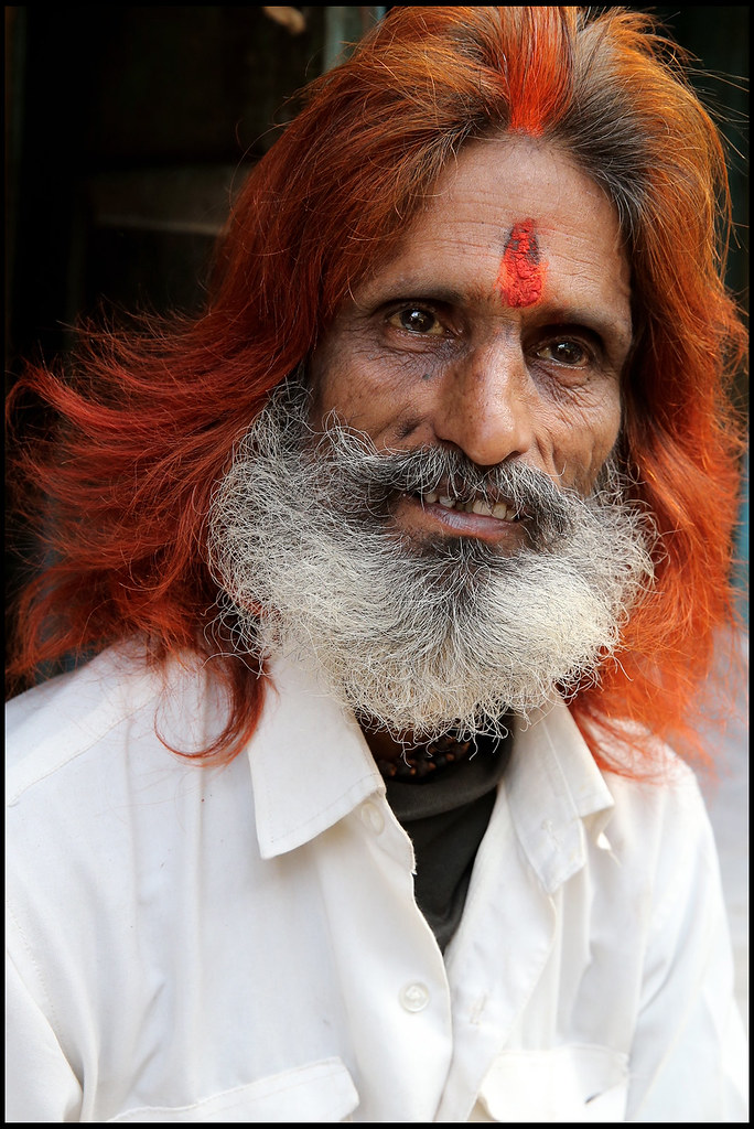 man with hair dyed with henna on a street of Lucknow, Indi ...