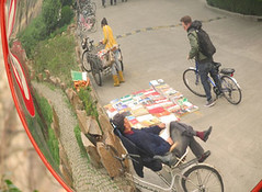This photo depicts Chinese cultural means of doing business. Next to the river on campus, the old man set up various books for sell to students. This could probably be seen as a mobile library. The bike nearby uses to transport all of these books. This pi