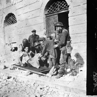 First-aid personnel of the Three Rivers Regiment placing Sergeant Johnny Marchand on a stretcher, Ortona, Italy... / Des secouristes du régiment de Trois Rivières placent le sergent Johnny Marchand sur une civière à Ortona (Italie)...