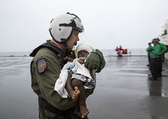 Hospital Corpsman 1st Class Matthew Hawkins, assigned to Helicopter Sea Combat Squadron (HSC) 21, assists an infant aboard USNS Mercy (T-AH 19). (U.S. Marine Corps/Sgt. Valerie Eppler)