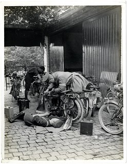 A dispatch rider [of the Indian Corps] repairing motor cycle [Merville, France]. Photographer: H. D. Girdwood. | by The British Library