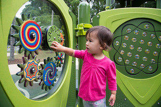 Girl playing with sensory panels in playground | by Brisbane City Council