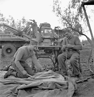 Private W. A. Lloyd repairs a tarpaulin while Lance-Corporal W. L. Milburn mends rope... / Le soldat W. A. Lloyd remet une bâche en état pendant que le caporal suppléant W. L. Milburn répare une corde...