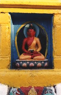 Statue of a red Buddha holding a begging bowl, blue and yellow aura, pink, orange, and blue lotus, stupa niche, vajra, Swayambhunath, Kathmandu, Nepal