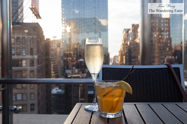 Glass of Prosecco and Sunny Honey cocktail with a view of the sunset