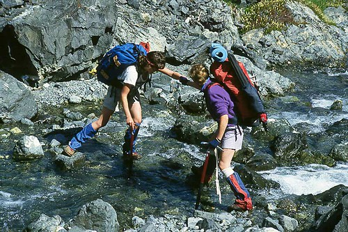 Backpackers cross the Elk River in Strathcona Provincial Park on Vancouver Island, British Columbia, Canada