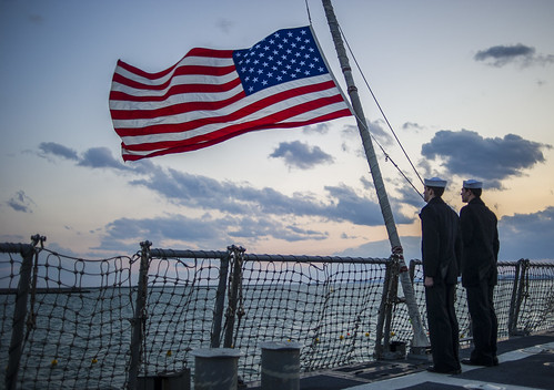 Sailors  lower the ensign during evening colors. | by Official U.S. Navy Imagery