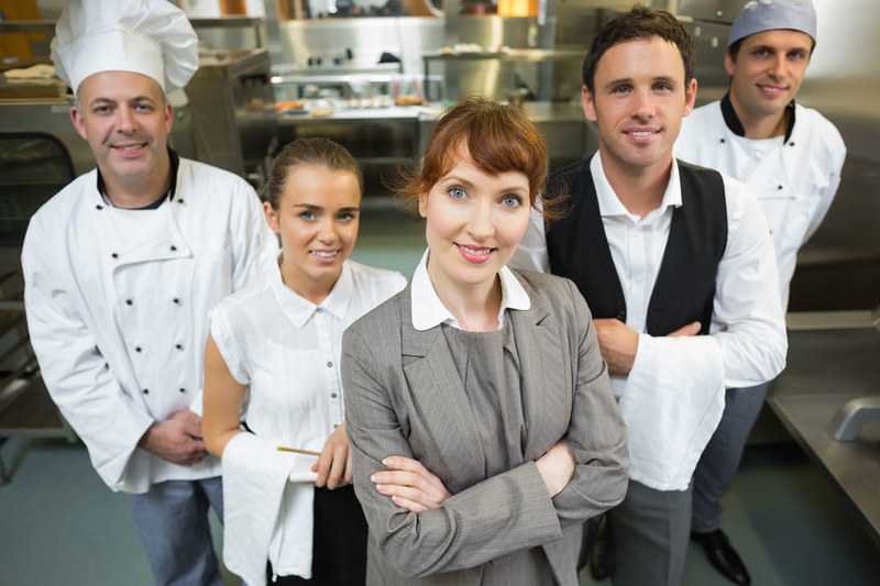 manager posing with the staff in a modern kitchen catering