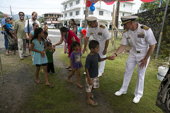 Capt. James Meyer, right, commodore of Task Force Forager, and Capt. Erich Diehl shake hands with local children during an Independence Day celebration in Kolonia, July 4. (U.S. Marine Corps/Sgt. James Gulliver)
