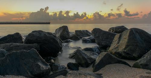 ocean sun water sunrise stones rays