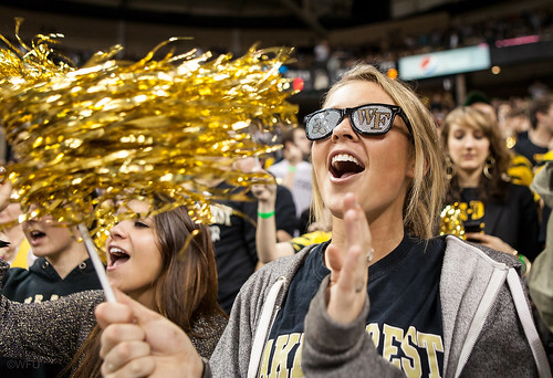 A fan cheers on the men's basketball team