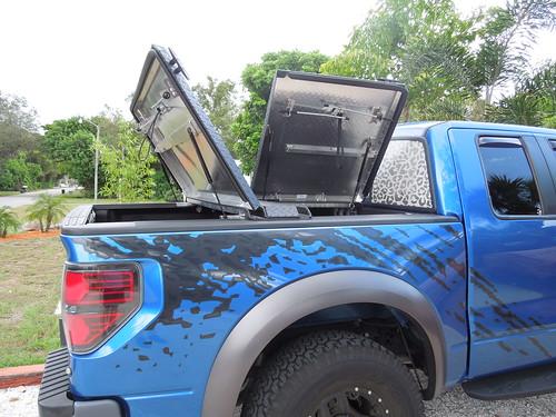 ford aluminum c pickuptruck f150 raptor cleat diamondback bluetruck diamondplate ff09 tonneaucover truckbedcover passengersideview twopanelsopen blacklinex ruggedblack addedcleats
