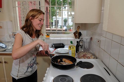 A student cooks a meal at an overseas residence house.