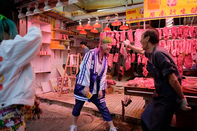 the butcher move a pig tongue towards the japanese tourist