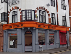 "A ground-floor shop at the end of a terrace.  The main part of the façade is grey on both front wall and side wall, while the sign above has black lettering (""Supreme Butchers"") on an orange background.  The arched shape of the doorway at the corner echoes brickwork arches on the first floor above."
