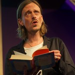 Mackenzie Crook reading on stage at the Edinburgh International Book Festival |