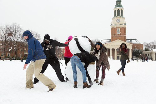 Students build a snowman on the quad