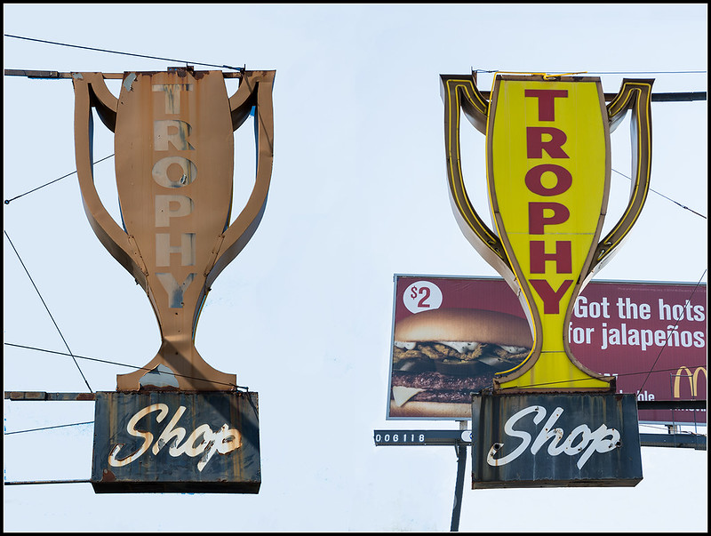"The sign for a trophy shop - there are two matching signs, shaped like a trophy saying ""trophy"" down the front and then shop underneath."