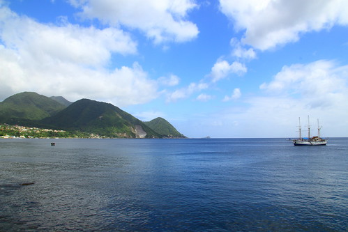 blue sea sky mountains water clouds boat line shore dominica roseau carbbean