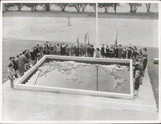 Mr. N. R. Jones takes a class in Geography at the concrete relief map of the world in the grounds of the May Road Primary School, Mt. Roskill, Auckland.