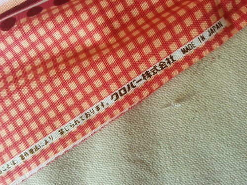 This fabric is a Clover quilting weight fabric with faux cross-stitch detailing of Little Red Riding Hood and the big bad wolf. If you happen to read Japanese, I'd love to have the exact text (plus a translation) so I can do a real search for more info on this fabric.  I didn't use this fabric in Sunshine, exactly; I used the Cinderella fabric from the same line, but I do not have the selvage from it.