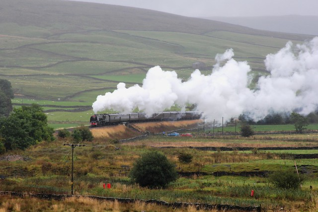 Stanier LMS8P Pacific No. 46233 'Duchess of Sutherland' powers up the 1 in 100 Long Drag onto the short Level section at Helwith Bridge with RTC 'Cumbrian Mountain Express' through heavy rain on 6th September 2014 ©